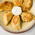 Easy homemade pierogies filled with two different fillings including cheddar mashed potato and caramelized onions with sauerkraut.
