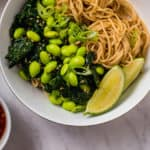 A cold Asian inspired soba noodle salad with garlic sauteed kale and edamame dressed in a creamy and gingery peanut sauce.