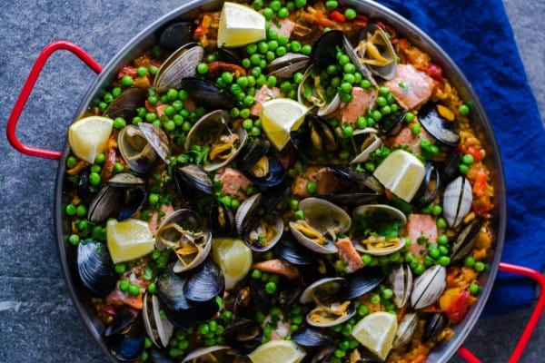 Seafood and chorizo paella is full of Pacific Northwest clams and mussels, wild salmon, spicy chorizo and garnished with sweet peas and bright lemon.