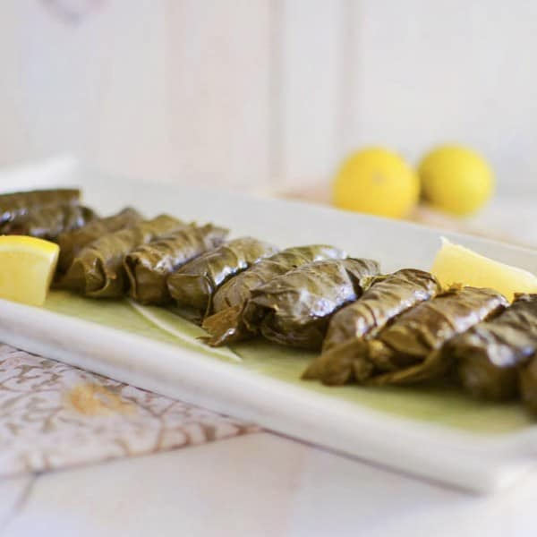 Step by step recipe on how to make Turkish stuffed grape leaves. Filled with meat and rice and simmered with layers of fresh lemon.