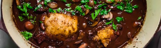 Step by step instructions for Julia Child's Coq Au Vin, with stewed chicken in a rich buttery red wine sauce with sauteed mushrooms and pearl onions.