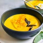 Thick and Creamy pumpkin soup with fresh roasted pumpkin is blended up with warm fall flavors of paprika and maple and topped with savory fried sage.