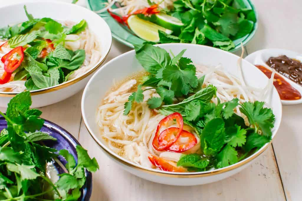 Veitnamese chicken pho aka pho ga is topped with thinly sliced chilis and fresh herbs.