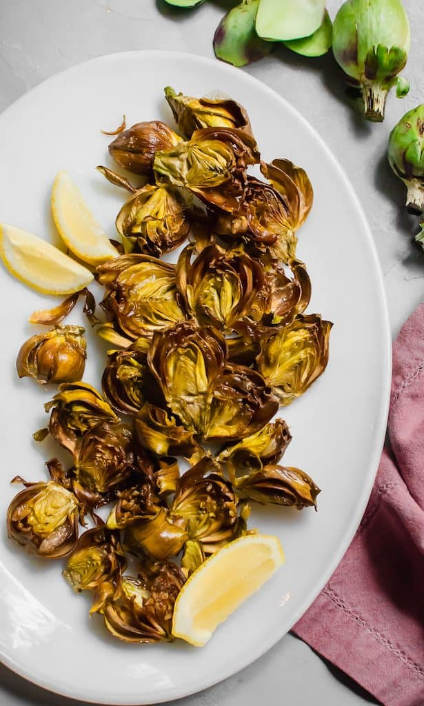 Baby artichokes are fried gently in olive oil until crisp and then seasoned simply with sea salt and lemon juice.