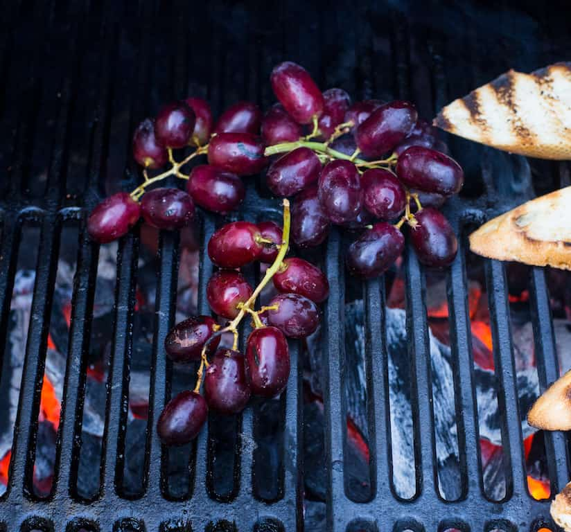 Grill grapes over a charcoal grill until the fruit is sweet and charred.