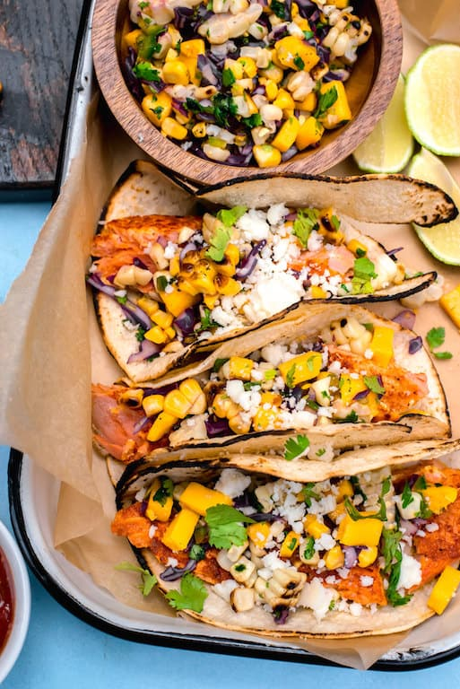 Get the grill going with sazon spiced salmon tacos, topped with a sweet and spicy colorful mango corn salsa for the perfect summer dinner.