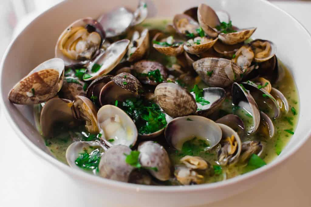 Steamed clams are cooked together with wine wine, garlic, a touch of butter and loads of fresh herbs. And have extra crusty bread ready to soak up the delicious broth.