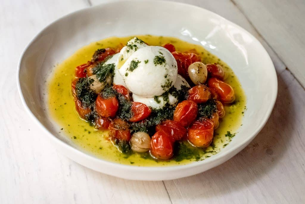 Slow roasted tomatoes are cooked with olive oil and garlic and served with a bright basil oil and creamy burrata.