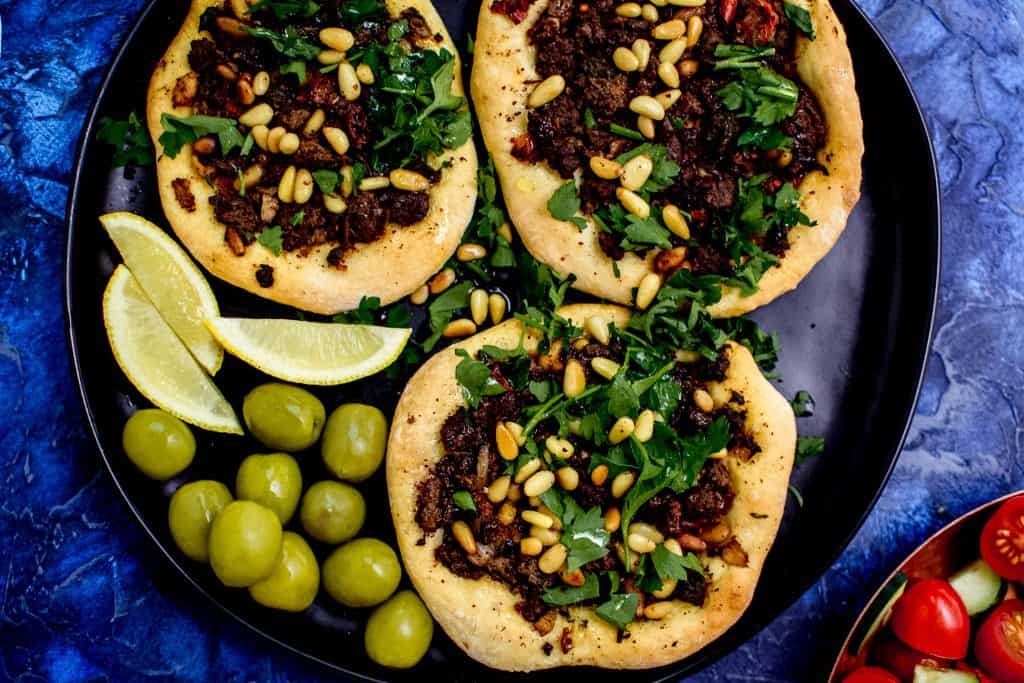 Inspired by the savory Lebanese meat pies called sfeeha, these open faced pies are topped with spiced beef or lamb and garnished with lemon and fresh herbs.