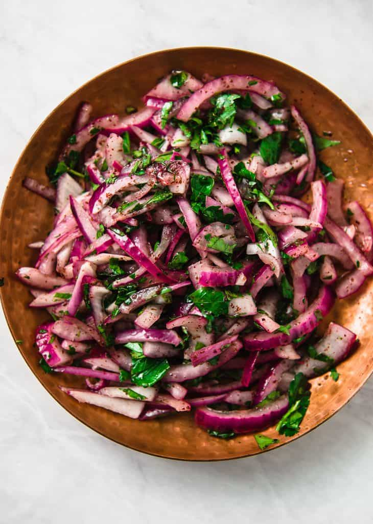 The perfect condiment to topped grilled meats, this Turkish sumac onion salad has thinly sliced red onions tossed with bright sumac, fresh parsley and fresh lemon juice.