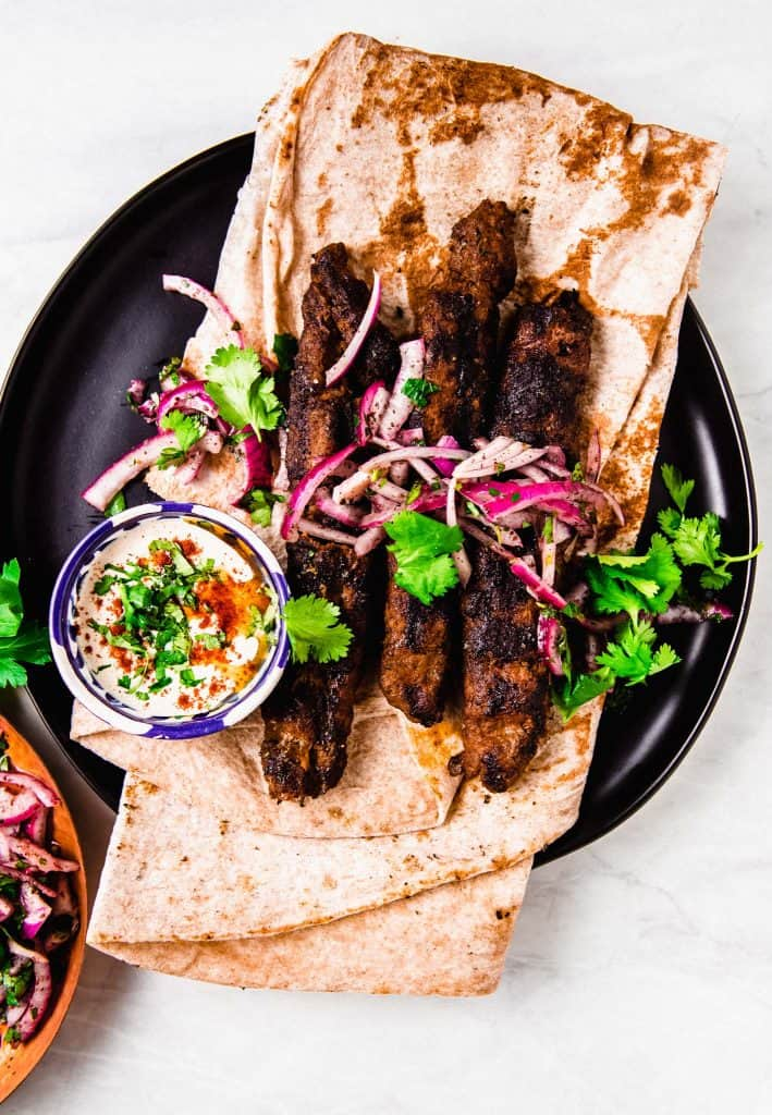 Kofta Kebabs are a popular and flavorful Mediterranean street food. Ground beef and lamb are flavored with aromatic spices and fresh herbs and pressed onto skewers before being grilled over charcoal. Serve with creamy tahini sauce and sumac onion salad.