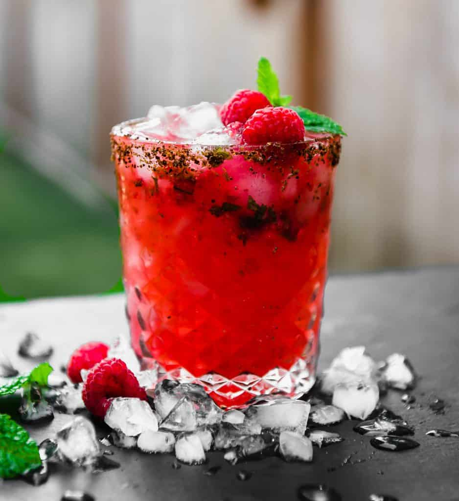 Smoky, slightly sweet and a bit tart, this  refreshing mezcal cocktail is muddled with fresh raspberries and mint and garnished with a Tajin rim.