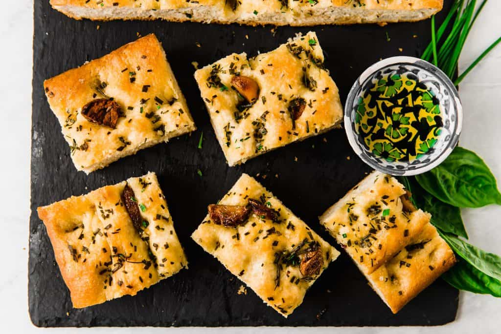 Savory and sweet roasted garlic is nestled into airy focaccia and topped with garlic oil, loads of fresh herbs and flaky sea salt.