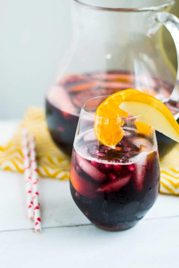 A fall twist on the traditional sangria, this pear and pomegranate sangria is mixed with pomegranate simple syrup, fresh pear slices and citrus that is not only delicious, but gorgeous too. #sangria #pomegranatesangria