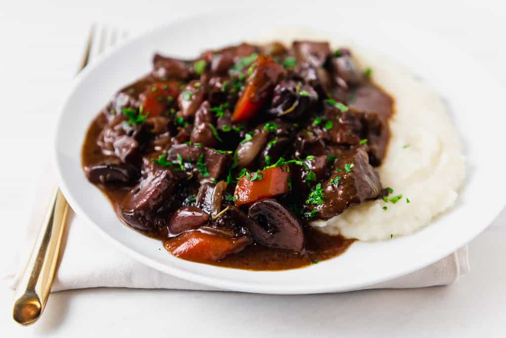 A slightly more simplified version of Julia Child's beef bourguignon recipe, with a rich red wine sauce and buttery herbed mushrooms.