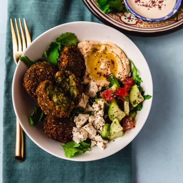 A flavorful and colorful falafel bowl filled with fresh greens, Israeli chopped salad, homemade falafel and finished with a creamy tahini yogurt sauce.