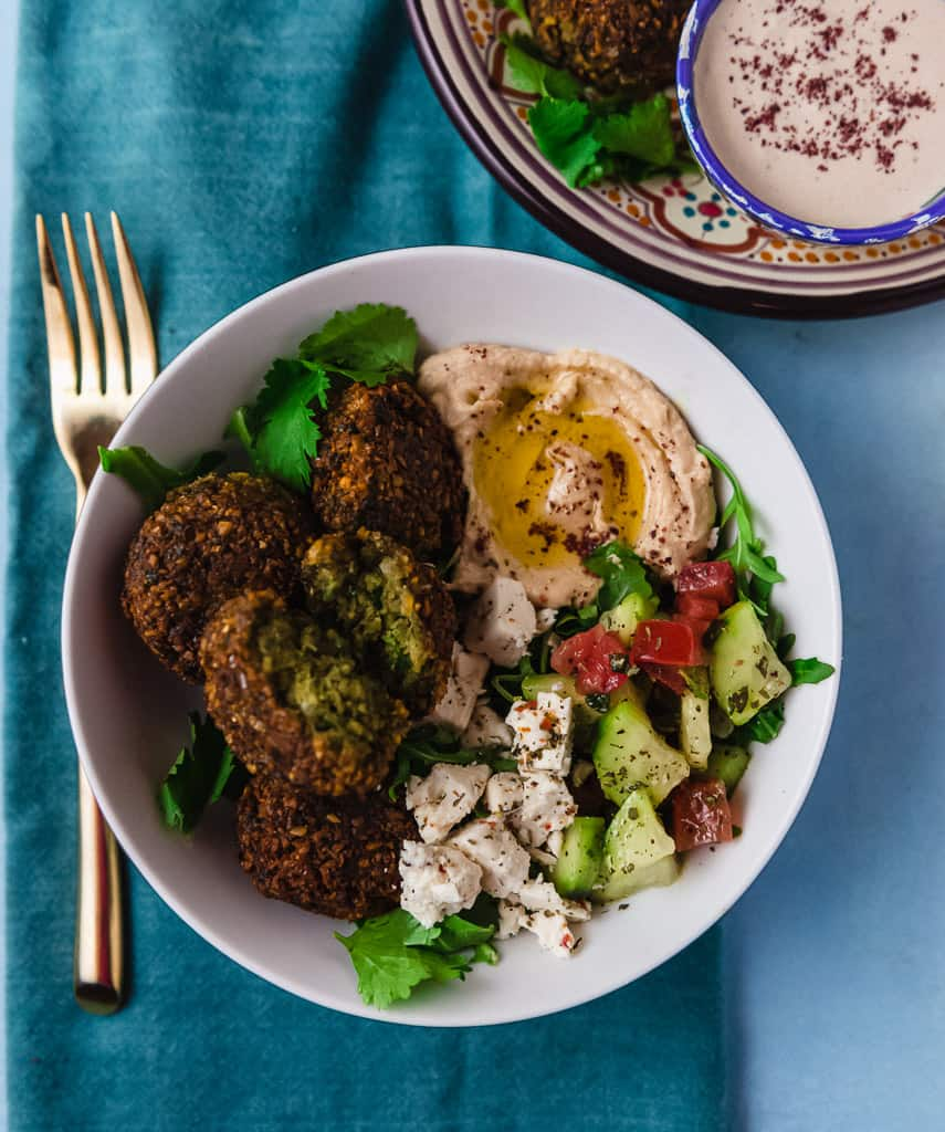 A flavorful and colorful falafel bowl recipe filled with fresh greens, Israeli chopped salad, homemade falafel and finished with a creamy tahini yogurt sauce.