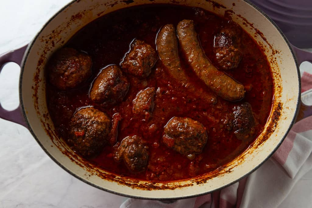 Homemade meatballs with Sunday gravy is a true labor of love. Meatballs are mixed with three meats and seasoned with flavorful aromatics which are then simmered in marinara for hours making them incredibly tender and flavorful.