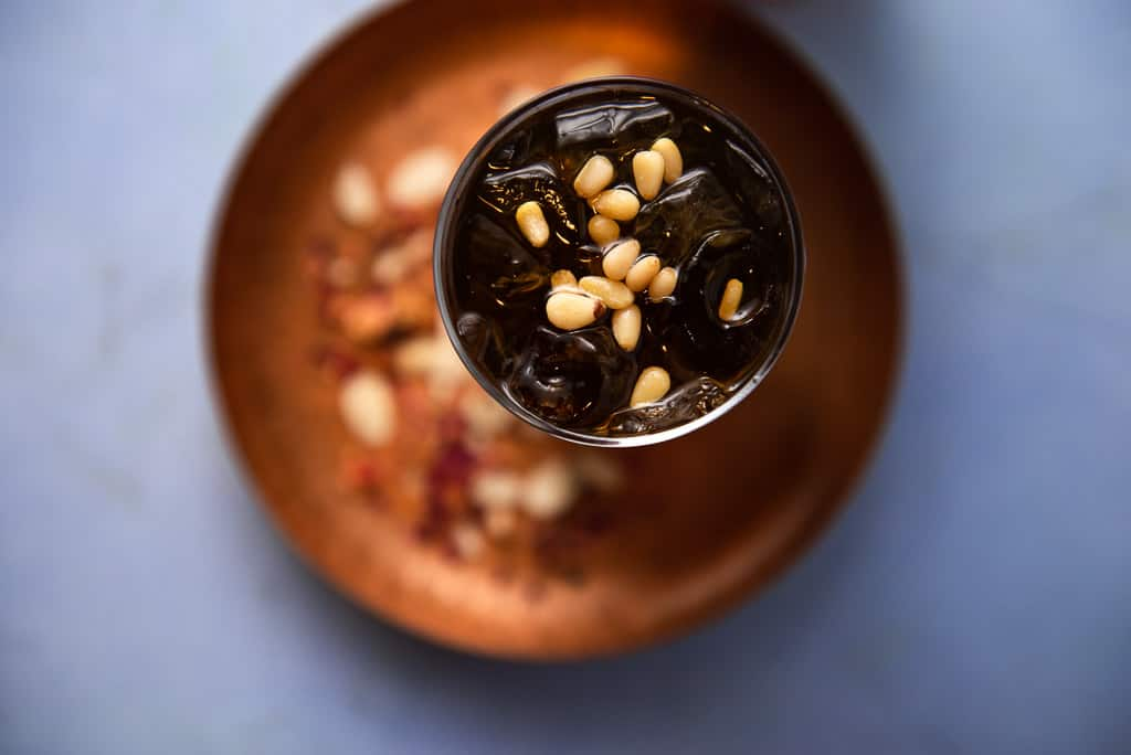 A floral and refreshing Middle Eastern drink inspired from Lebanon, Jallab is made with date molasses, a touch of rose mater and topped with pine nuts.