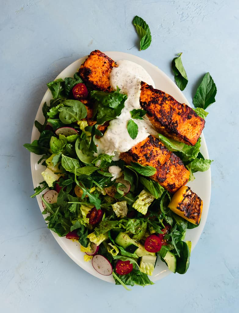 Inspired from bold flavors of chicken shawarma, this salmon shawarma salad uses the same marinade for intense flavors. Served on top of a crisp crunchy salad  and finished with a creamy dill sauce.