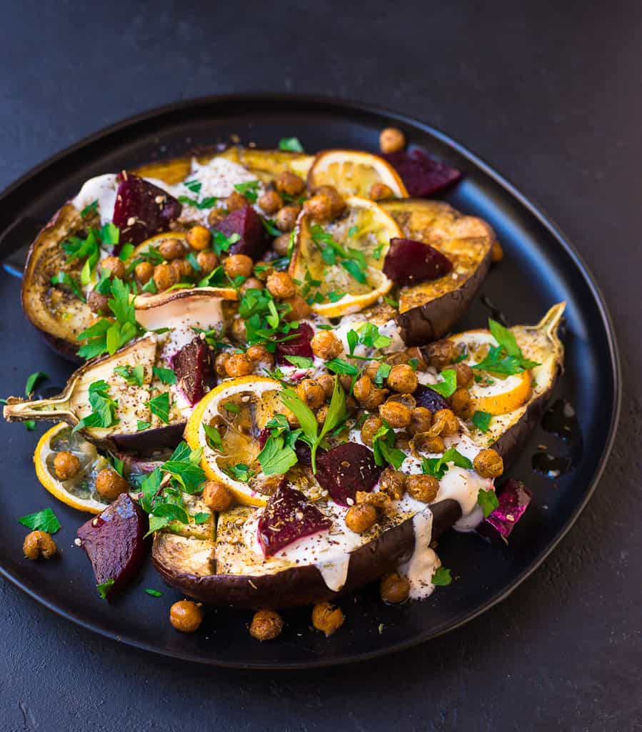 Roasted eggplant is topped with creamy tahini, sweet beets and roasted chickpeas that is hearty enough as a Mediterranean vegetarian entree.