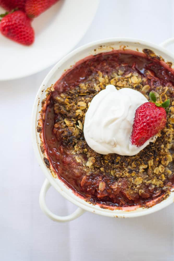 Strawberry crumble is topped with a hazelnut and oat topping and finished with a cool and creamy coconut whipped cream.