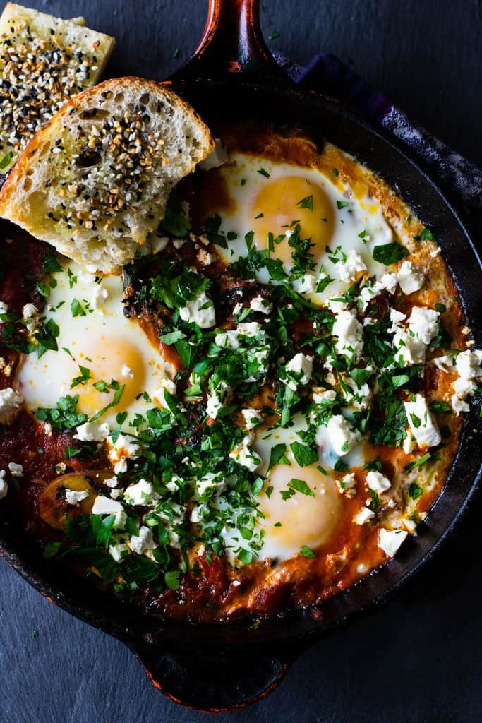 A hearty and smoky vegetarian shakshuka recipe loaded with sauteed kale, mushrooms and peppers. The tomato is seasoned with deep spices of cumin and paprika and once the dish is just done cooking, everything is topped with creamy feta and lots of fresh herbs.