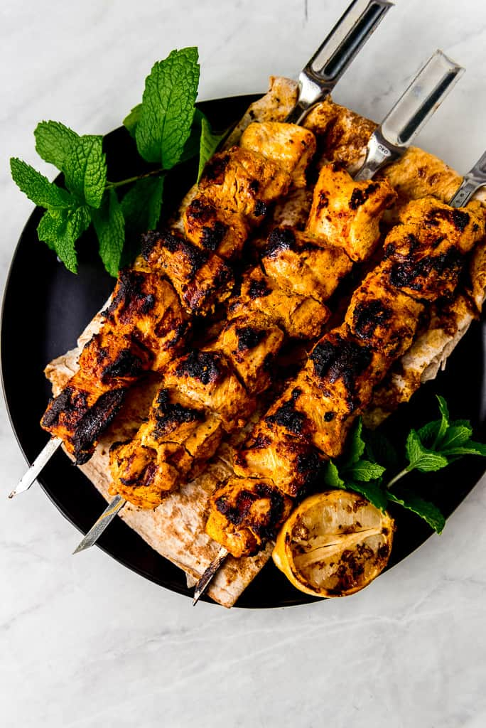 """Shish tawook literally translates to """"chicken skewers"""" and is widely known in Lebanese and Middle Eastern cuisine. Chicken thighs marinate in a mixture of yogurt, lemon and warm spices before being grilled over charcoal to create the most tender, juicy and flavorful chicken. This will become your favorite skewer recipe and is perfect served over lavash or salad."""