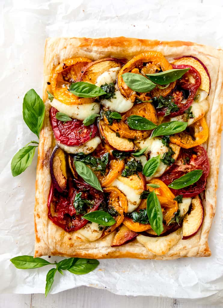 Peach caprese tart with heirloom tomatoes, mozzarella and peaches layered on top of buttery puff pastry and finished with basil and balsamic.