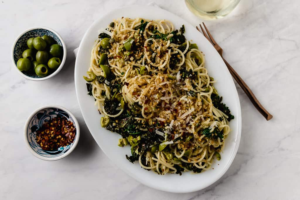 Kale pasta with capers and olives is a lighter version of puttanesca pasta, with buttery castelveltrano olives and topped with toasted panko.