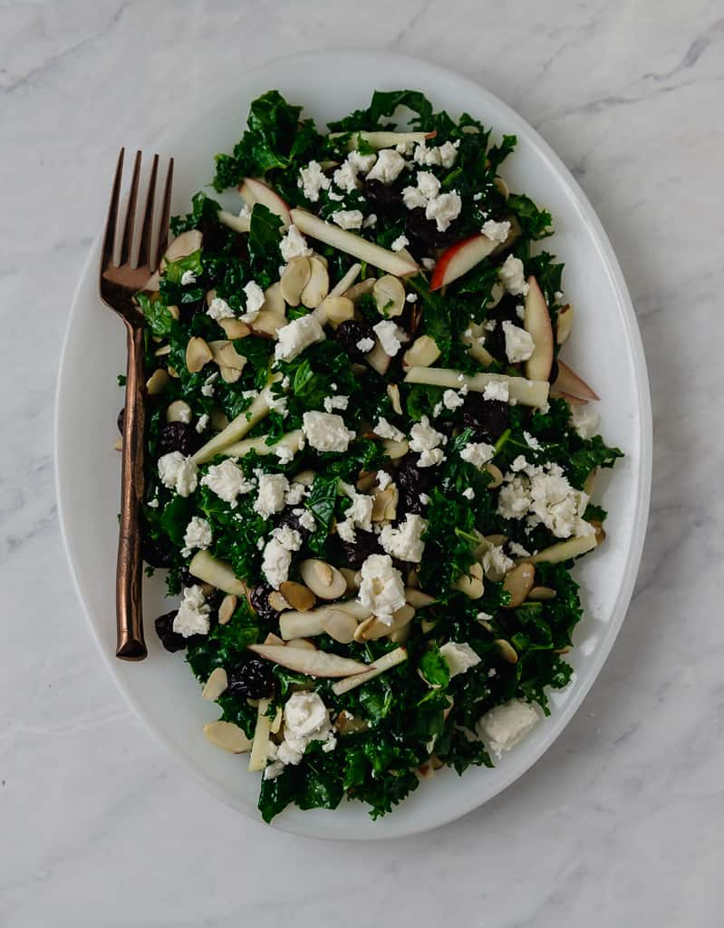 Kale cranberry salad  is tossed with a slightly sweet maple Dijon dressing, dried cranberries, creamy feta, apples and toasted almonds.