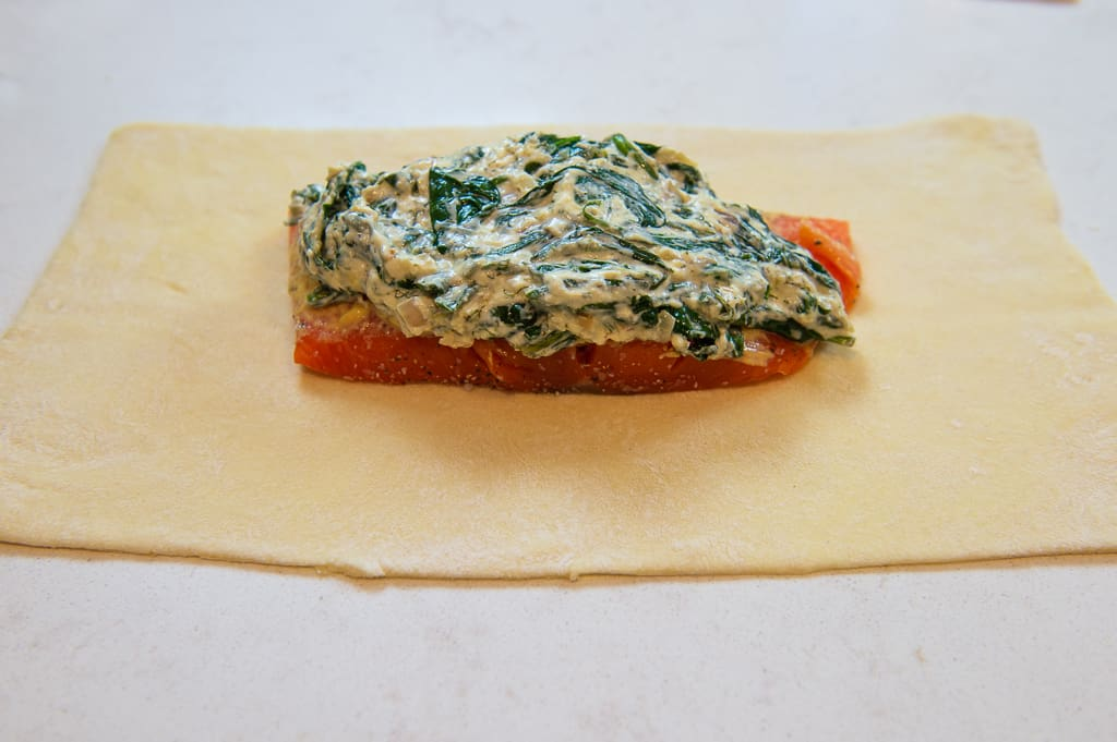 Unbaked salmon wellington with a filet of salmon centered on top of thawed puff pastry and layered with a creamy spinach mixture.