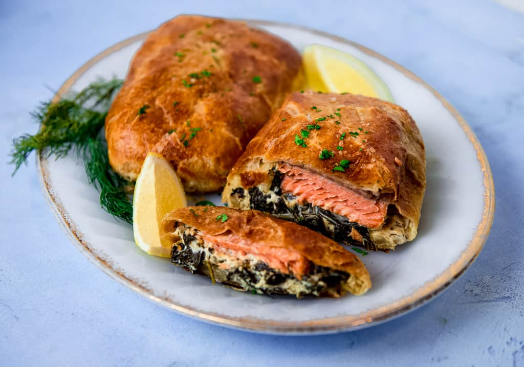 Salmon wellington is a filet of salmon, layered with a creamy spinach mixture and wrapped in puff pastry. The salmon wellington is baked until perfectly golden brown.